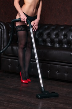 Sexy maidservant with vacuum cleaner in living room
